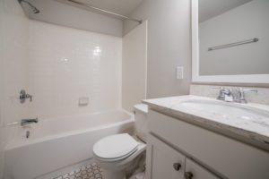beautiful tiled bathroom with granite countertops