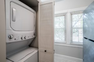 stacked laundry unit underneath white tiled floor