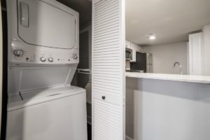 stacked laundry units tucks away next to kitchen