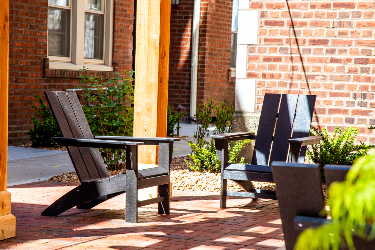 Adirondack Chairs sit under pergola near apartments